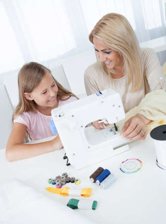 Portrait Of A Beautiful Young Girl Sewing With Her Mother At Home photo