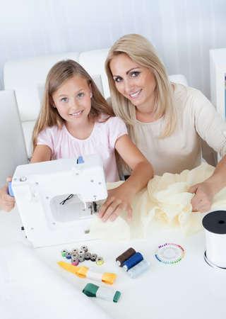 Retrato de una costura hermosa joven con su madre en casa photo