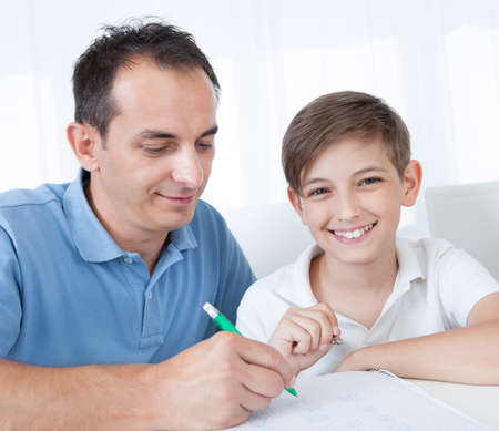 homework: Portrait Of Father And Son Doing Homework At Home Stock Photo