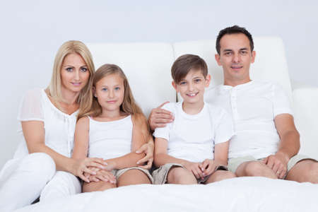 Portrait Of Happy Family With Two Children Sitting On Bed In Bedroom photo