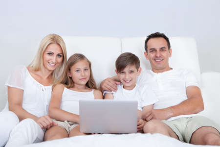 internet love: Portrait Of Happy Family With Two Children Sitting On Bed In Bedroom