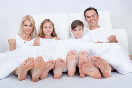 bed feet: Happy Family With Two Children In Bed Under Cover Showing Feet, Indoors Stock Photo