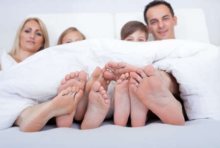 girls feet: Happy Family With Two Children In Bed Under Cover Showing Feet, Indoors Stock Photo