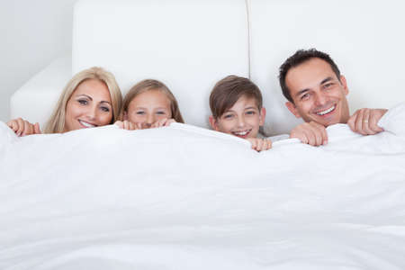 Happy Family With Two Children In Bed Under Cover, Indoors photo