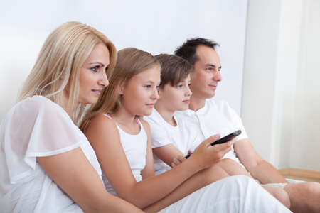 A Happy Family With Two Children Sitting In Bed Watching Tv At Home photo