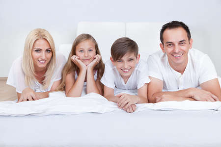 Happy Family With Two Children Lying On Bed At Home photo