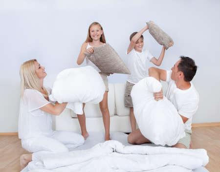 Familia Juguetón tener una pelea de almohadas junto en la cama en el dormitorio
