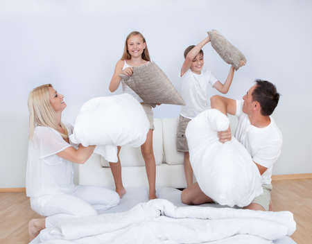 brother sister fight: Playful Family Having A Pillow Fight Together On Bed In Bedroom