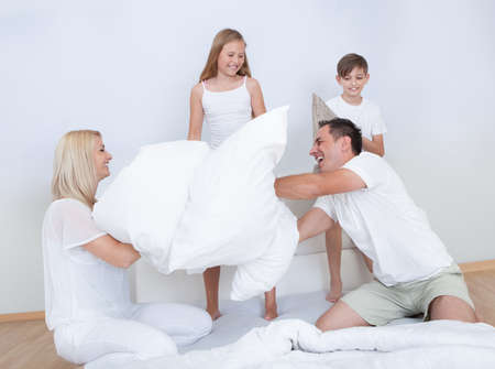 Playful Family Having A Pillow Fight Together On Bed In Bedroom photo