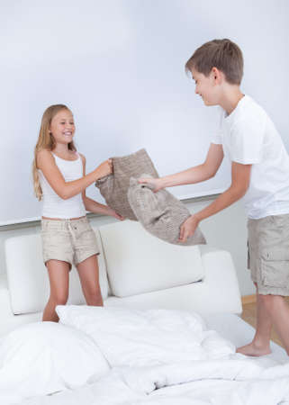 brother and sister: Siblings Having A Pillow Fight Together On Bed In Bedroom Stock Photo