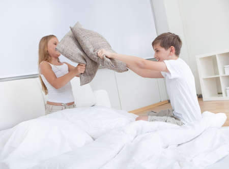 Siblings Having A Pillow Fight Together On Bed In Bedroom photo