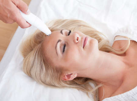 laser surgery: Profile View Of Happy Young Woman During Cosmetic Treatment, Indoors Stock Photo