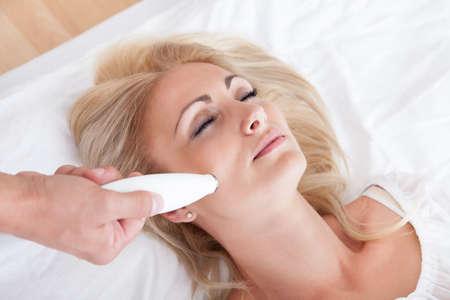 Profil nézet boldog fiatal nő közben kozmetikai kezelés, bent