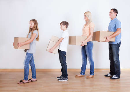 Parents And Two Children With Cardboard Boxes, Indoors Stock Photo - 15574850