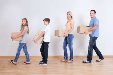 Parents And Two Children With Cardboard Boxes, Indoors Stock Photo - 15574842