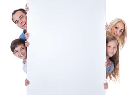 mother board: Portrait Of Family With Two Children Peeping Behind Blank Board On White Background