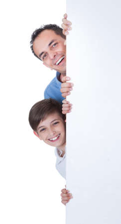 Portrait Of Father and Boy Peeping Behind Blank Board On White Background photo