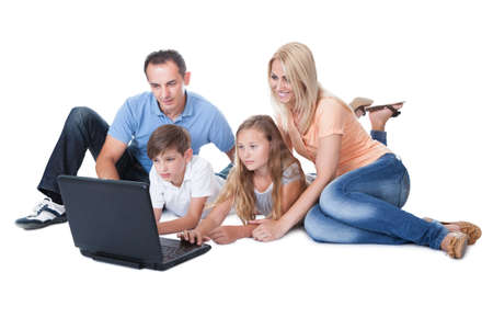 A Happy Family With Two Children Using Laptop Isolated On White Background Zdjęcie Seryjne