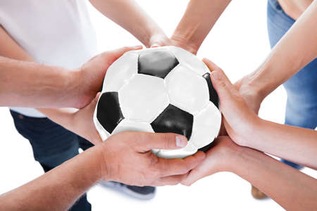 Several Hands Holding Together Soccer Ball Isolated On White Background photo