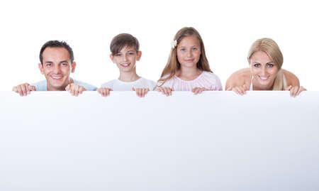 Portrait Of Familie mit zwei Kindern Behind Blank Board auf wei�em Hintergrund