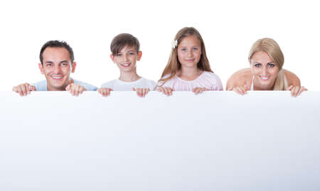 four poster: Portrait Of Family With Two Children Behind Blank Board On White Background Stock Photo