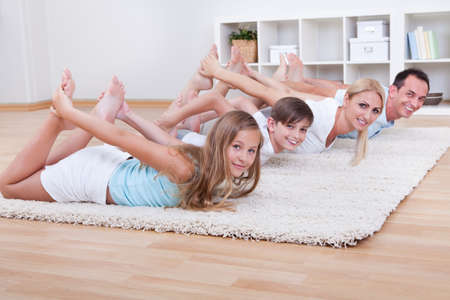 yoga man: Family Doing Stretching Exercises Laying On The Carpet At Home Stock Photo