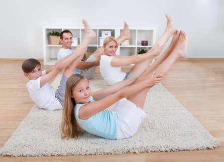 растягивание: Семья делает упражнения на растяжку лежа на ковер у себя дома