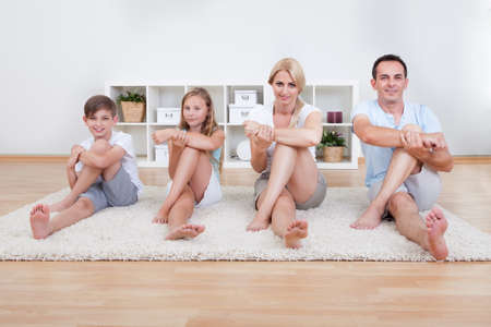Family Doing Stretching Exercises Laying On The Carpet At Home Stock Photo - 15574890