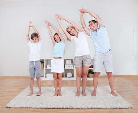 Familie doet rek-en strekoefeningen Op Het Tapijt Thuis Stockfoto