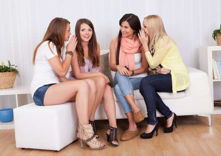 Four stylish attractive young women sitting on a couch sharing secrets photo