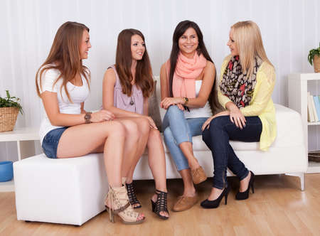 Row of beautiful stylish young ladies sitting on a couch in a living room photo