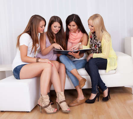 engrossed: Four elegant beautiful female friends sit on a couch with their heads close together looking at a folder Stock Photo