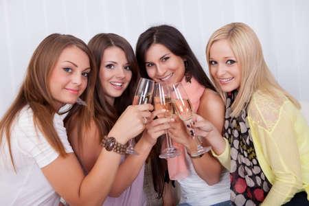 brindis champan: Grupo de chicas atractivas elegantes con encantadora sonrisa muy juntos brindando con champ�n