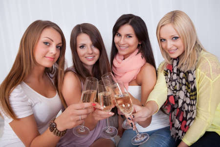 people partying: Group of attractive stylish girls with lovely smiles standing close together toasting with champagne
