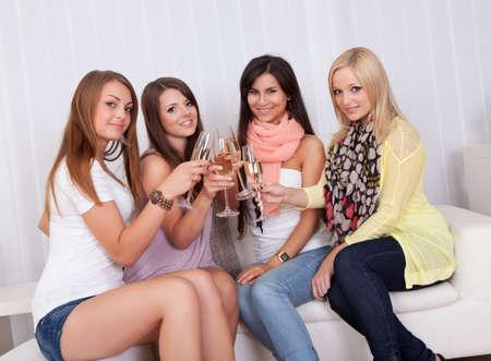 entre filles: Groupe de filles attirantes �l�gantes avec des sourires charmants debout pr�s les uns des toast avec du champagne