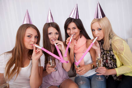 conical hat: Four attractive females celebrating with a champagne and cone caps Stock Photo