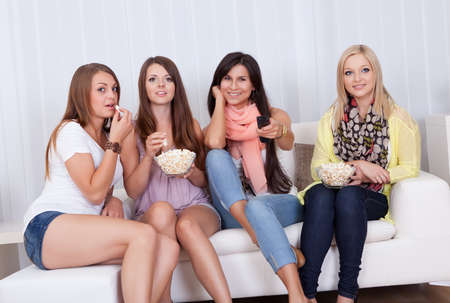 woman couch: Four beautiful women sitting on a couch together eating popcorn and watching television