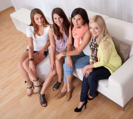 topdown: Row of beautiful stylish young ladies sitting on a couch in a living room