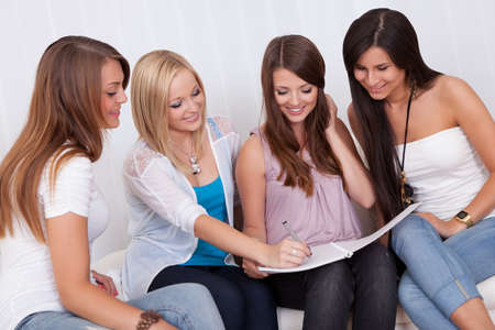 Four elegant beautiful female friends sit on a couch with their heads close together looking at a folder photo