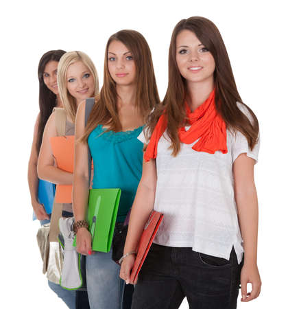 receding: Four beautiful young female students standing in a receding row with folders of notes under their arms isolated on white