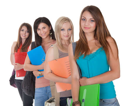 staggered: Four beautiful young female students standing in a receding row with folders of notes under their arms isolated on white