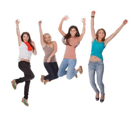 socializando: Cuatro mujer emocionada joven que salta para la alegría con sus manos levantadas en el aire en la celebración aislados en blanco Foto de archivo