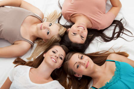 socializing: Overhead view of the faces of four attractive girls lying on the floor looking up with their heads close together
