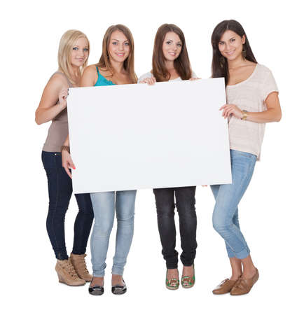 women jeans: Studio shot of four attractive girls with a blank white board isolated on white