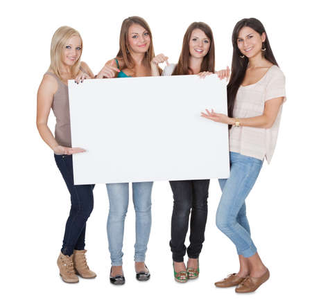 Studio shot of four attractive girls with a blank white board isolated on white Stock Photo - 15719997