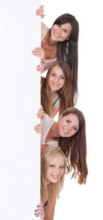 peering: Four beautiful long-haired women peering around the edge at a blank sign with copyspace for your text