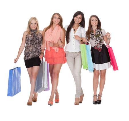 Cuatro mujeres felices con bolsas de la compra aislados en blanco