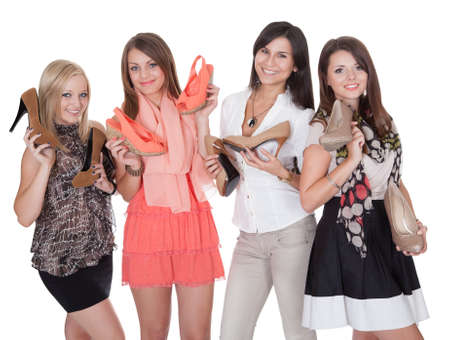 Four fashionable girls holding their shoes isolated on white Stock Photo - 15720037