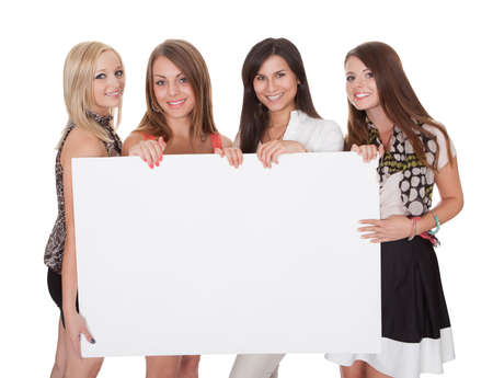 endorsement: Four attractive smiling young women with a blank white sign with copyspace for your text Stock Photo