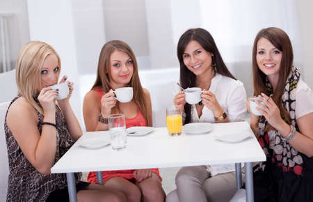Four stylish young woman having coffee seated at a table with rows of colorful shopping bags on the floor beside them photo